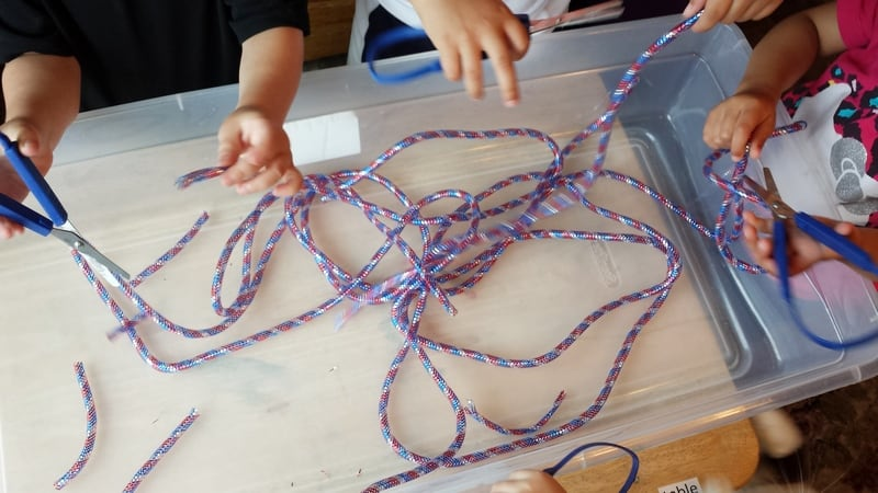 mesh tube ribbon sensory bin cutting activity 1