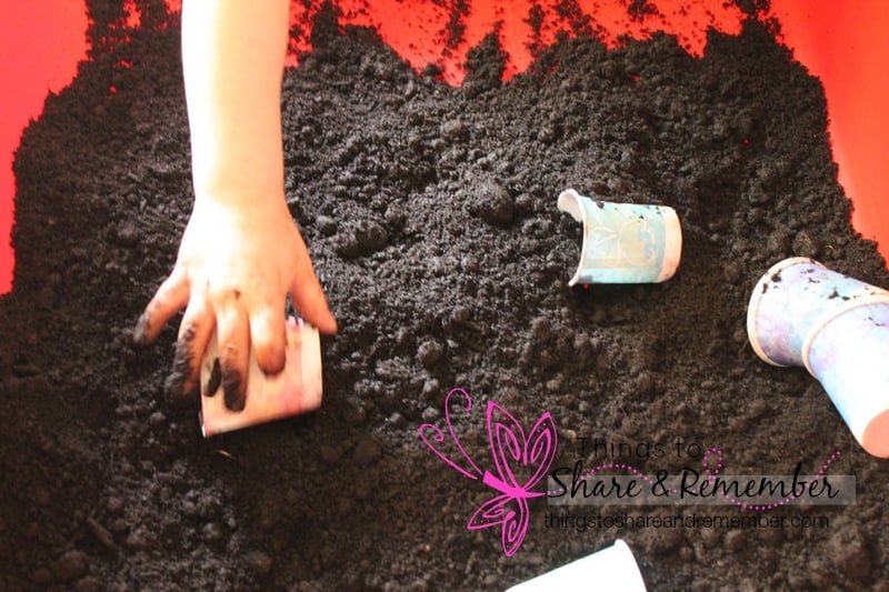 scooping soil sensory play