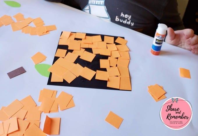 Child gluing orange squares to black square.