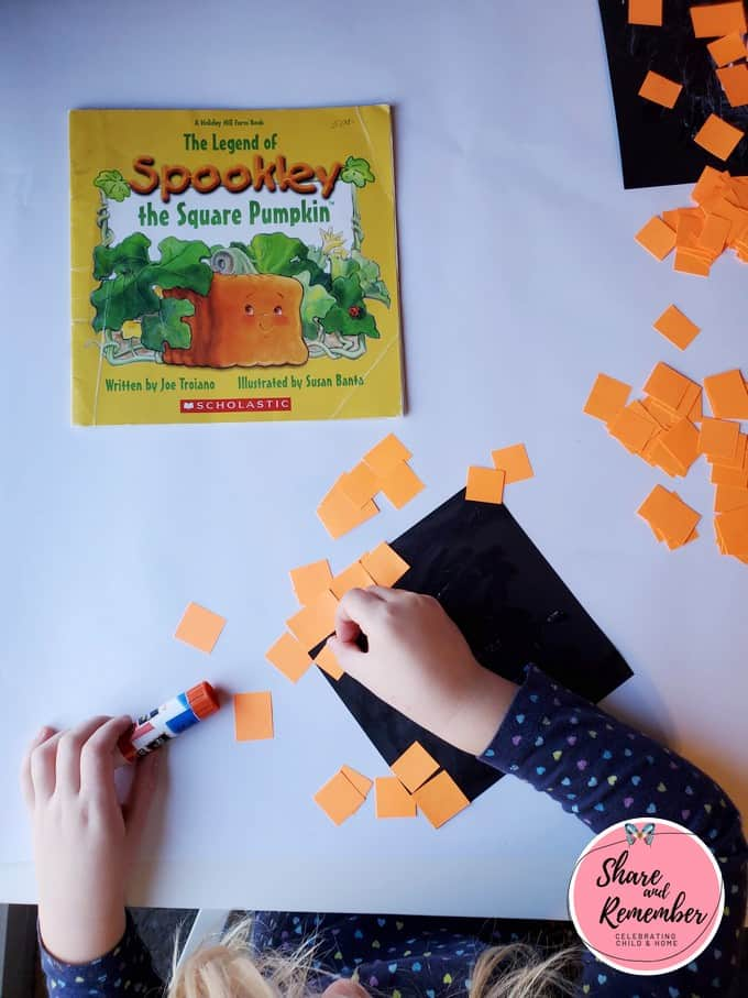Child gluing Spookley the Square Pumpkin Craft.