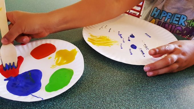painting with a wooden fork and tempera paint