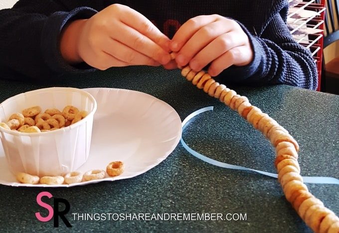 threading cereal onto pipecleaner bird feeder