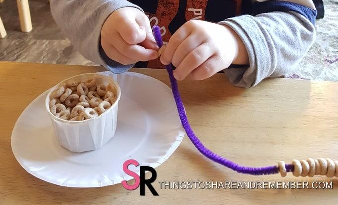 child making a bird feeder with cheerios