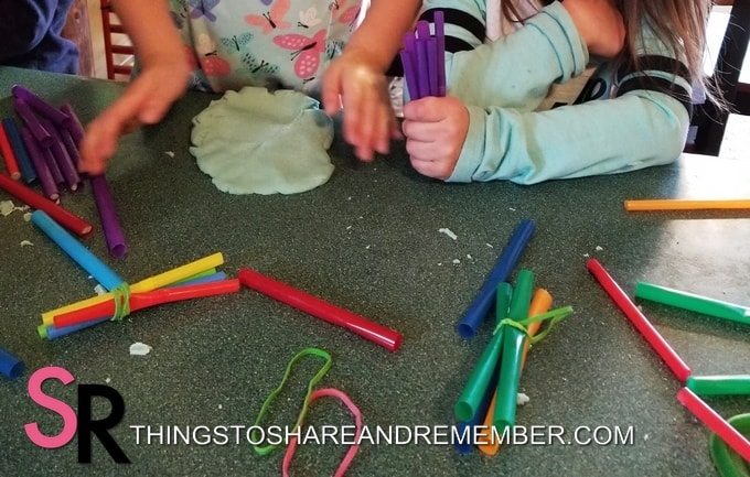 children playing with play dough and straws