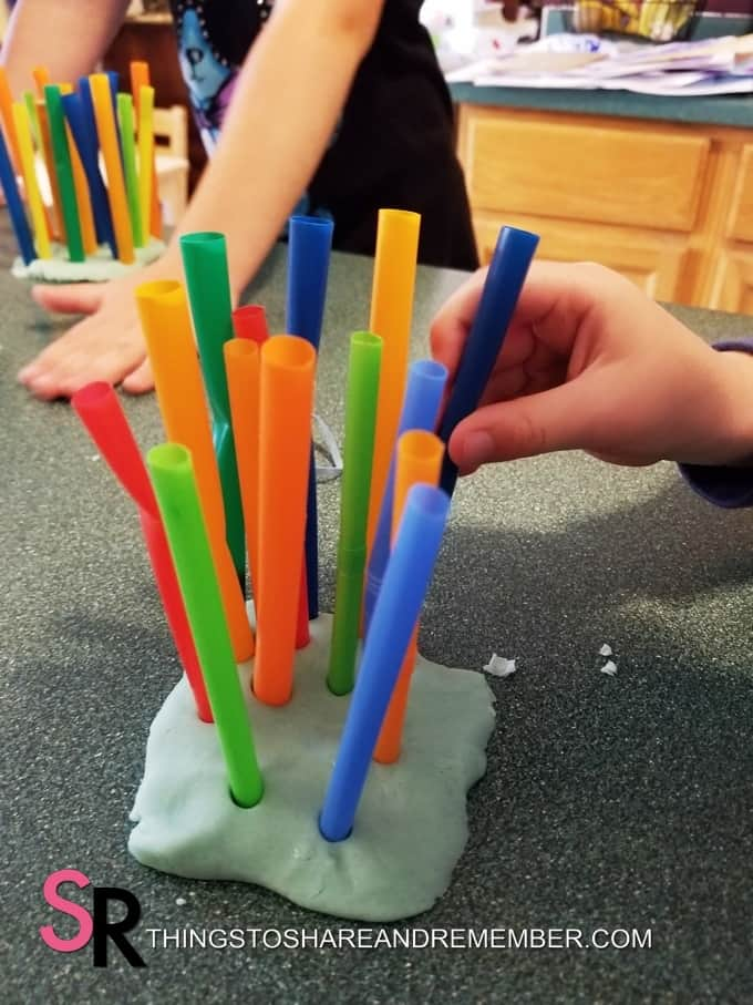 sticking straws into play dough