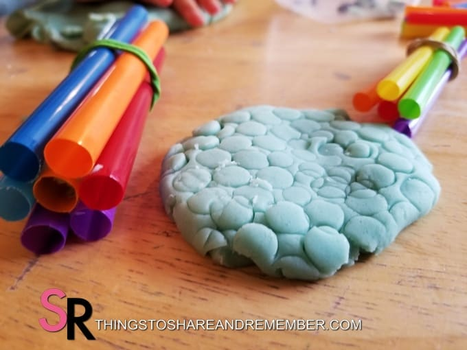 straws wrapped with rubber bands and play dough