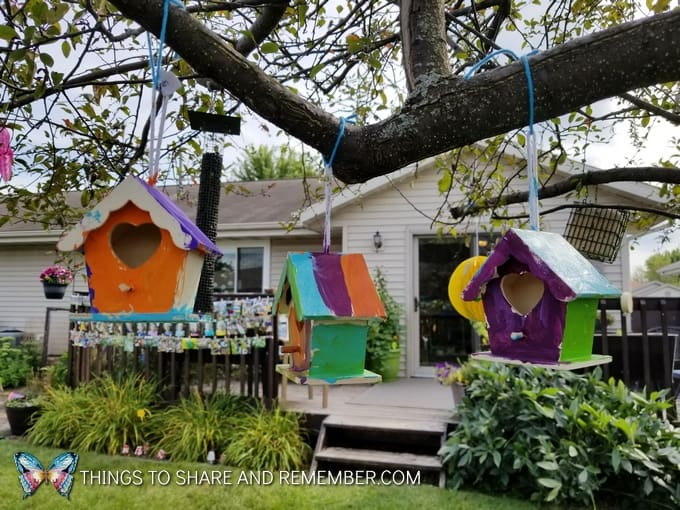 child painted birdhouses hanging in tree