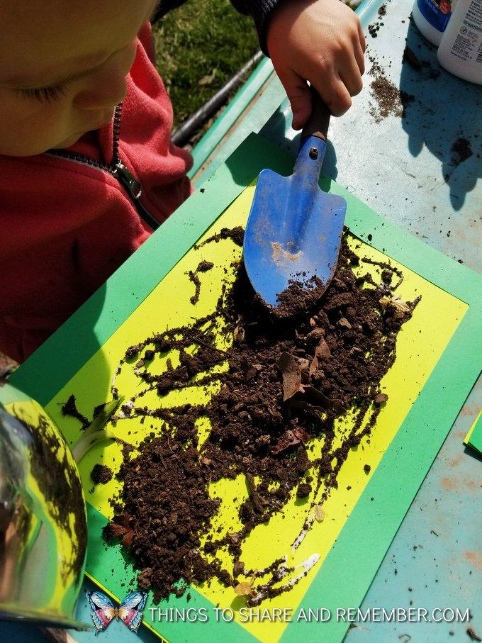 child spreading soil on green paper art
