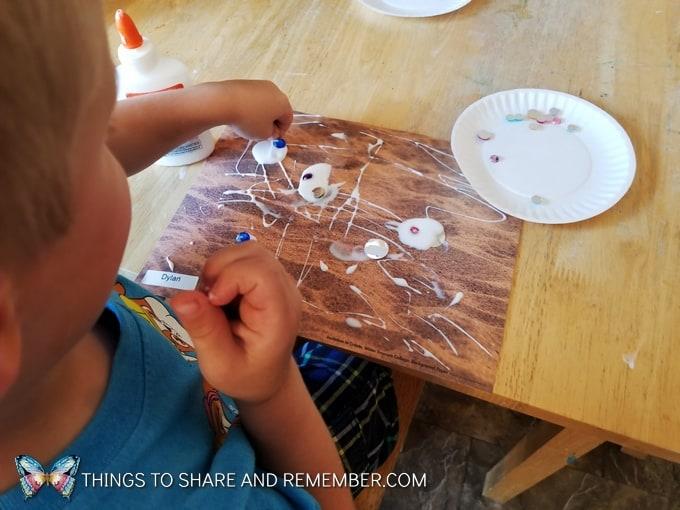 gluing gems on paper in preschool