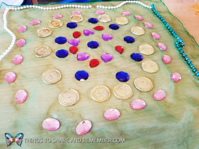 using beads, gems, and plastic coins on scarves in loose parts play