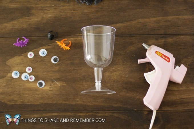 googly eyes, halloween bat and spider rings, plastic goblet, glue gun supplies to make Simple dollar store craft for Halloween Monster Party Cups Dollar store plastic wine cups decorated with googly eyes and plastic spider rings for child or adult Halloween parties