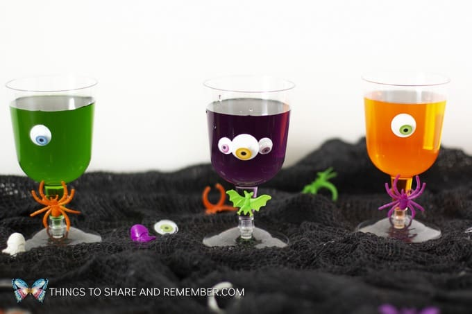3 cups of colored juice or soda in plastic wine cups decorated with googly eyes and spider or bat rings for Halloween party