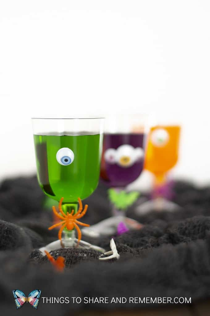 Green drink in plastic cup decorated with googly eyes and orange plastic spider for Halloween party