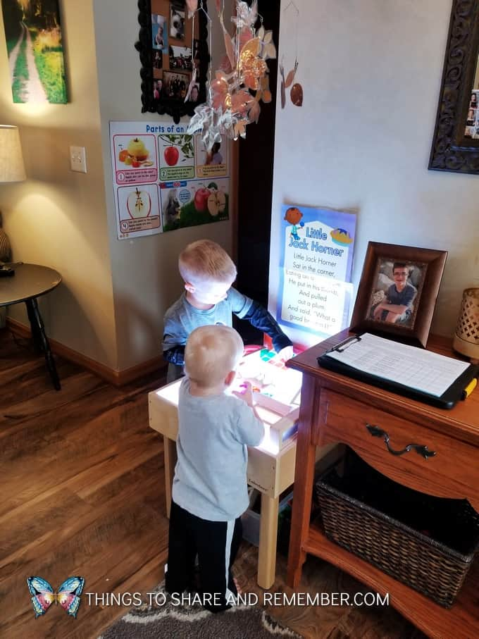 children playing on the light table in home child care environment