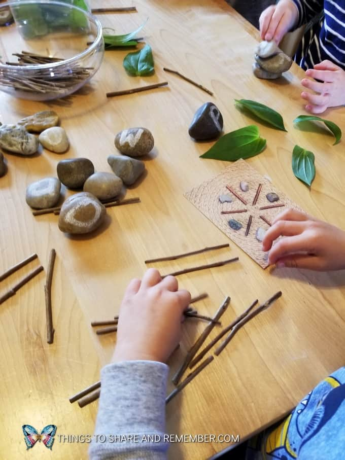 kids making Loose Parts Nature Designs with rocks, leaves and sticks