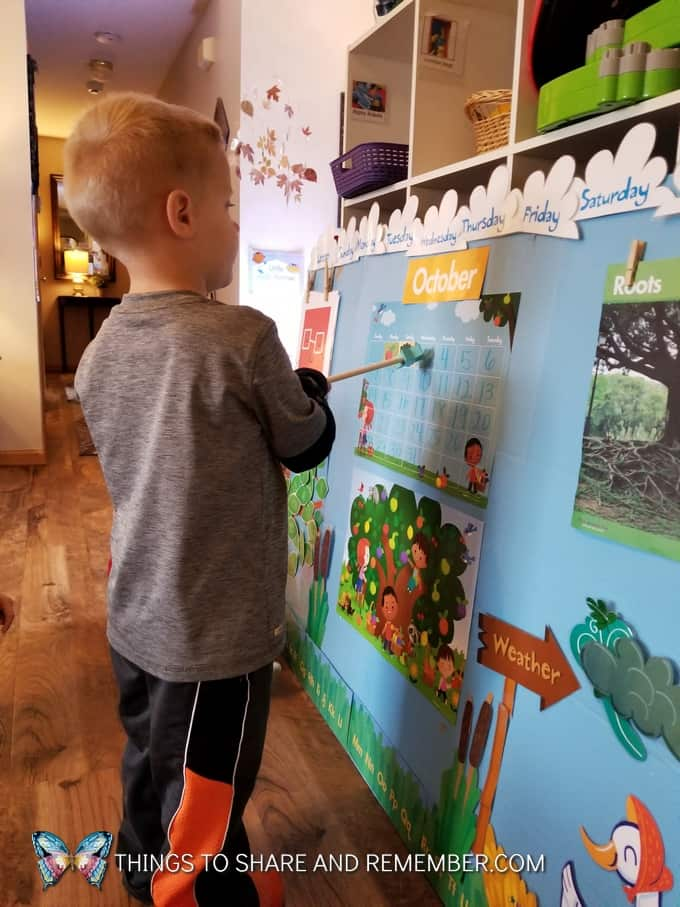 child pointing to the calendar with pointer super fun circle time