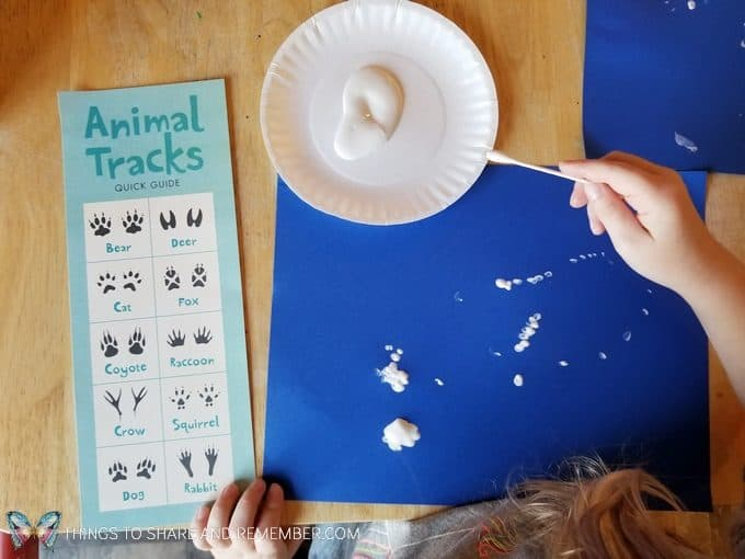 Animal Tracks art with paint and q-tips making tracks on blue paper  from Mother Goose Time Sights and Sounds #MGTblogger #MotherGooseTime #preschool #SightsandSounds