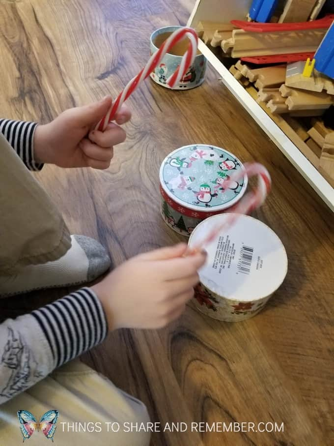 Tapping on boxes with plastic candy canes to create his own unique drum and sound. #MGTblogger #MotherGooseTime #preschool #SightsandSounds