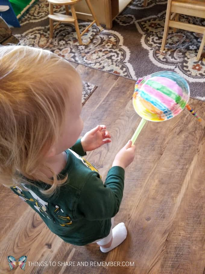 Pellet Drum instrument made from paper plates, straw, yarn and beads. #SightsandSounds #MotherGooseTime #preschoolactivities #musicforkids #MGTblogger