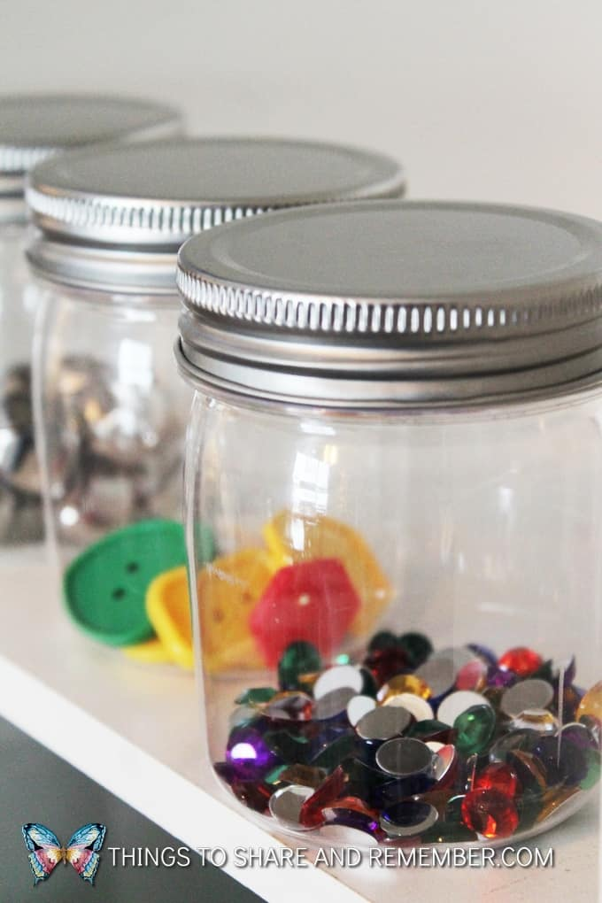 Sound shaker sensory jars for toddlers and preschoolers to experience different sounds and intensities we can make with objects - one jar contains gems, another large colorful buttons and the last jar has jingle bells to shake. #MGTblogger #MotherGooseTime #preschool #sensory #SightsandSounds #STEAM #preschoolSTEAM #STEAMStation