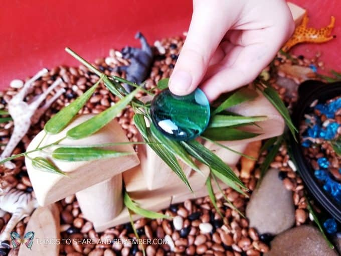 making a safari habitat Safari Habitat Sensory bin with animals for preschoolers Going on Safari theme from Mother Goose Time preschool curriculum #MGTblogger #MotherGooseTime #preschool #GoingonSafari #sensorybin #sensoryplay #smallworld #invitationtoplay