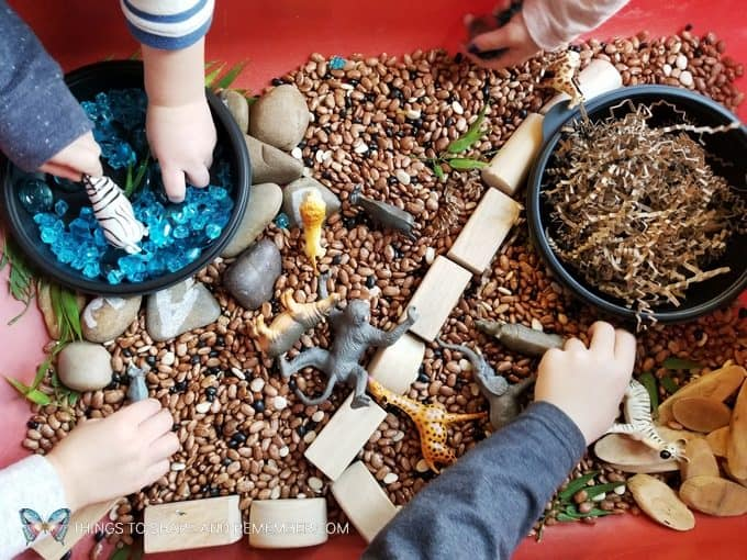 children playing with safari habitat sensory bin Safari Habitat Sensory bin with animals for preschoolers Going on Safari theme from Mother Goose Time preschool curriculum #MGTblogger #MotherGooseTime #preschool #GoingonSafari #sensorybin #sensoryplay #smallworld #invitationtoplay