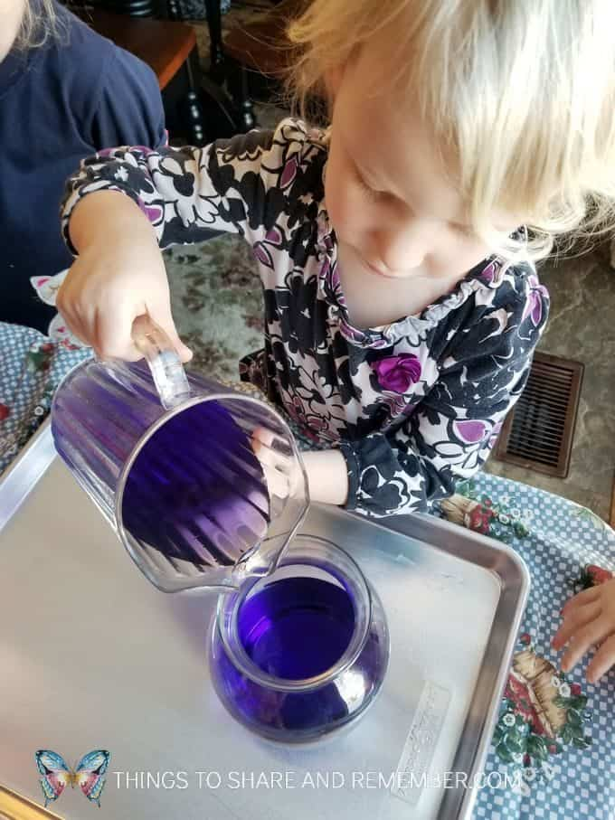Pouring Together Community Challenge from Mother Goose Time - pouring colored water from pitcher to vase measuring and pouring preschool activities