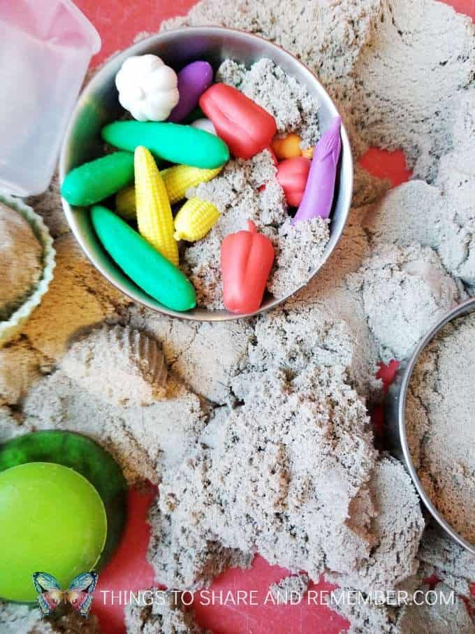 Kinetic sand sensory bin with Learning Resources Mix and Measure set and vegetable counters - for kitchen and baking preschool theme measuring and pouring preschool activities