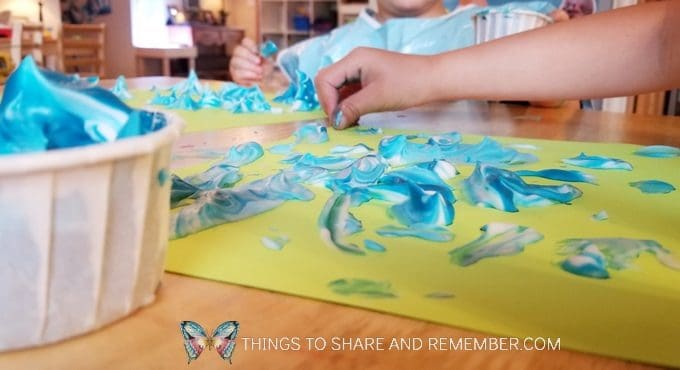 painting with blue paint and shaving cream on green paper