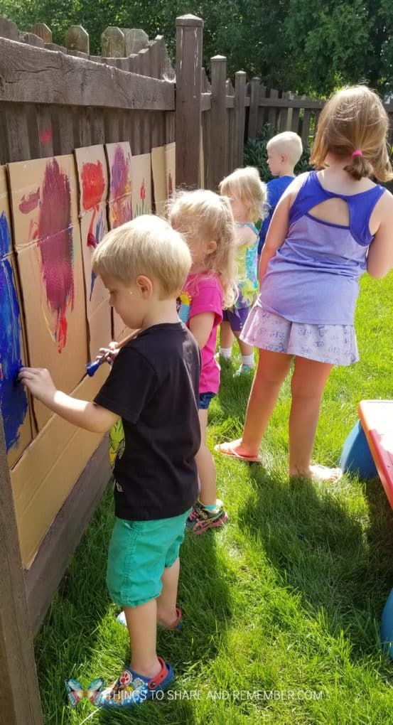 children painting on cardboard outoodrs