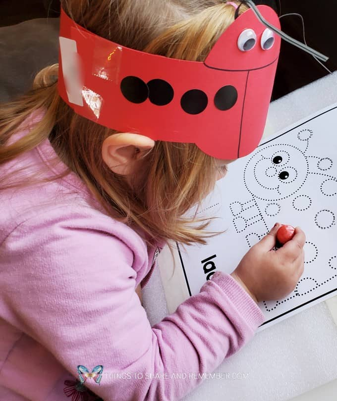 girl with ladybug headband working on ladybug art