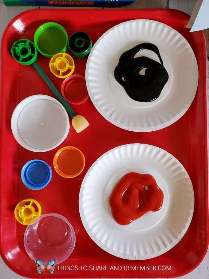 tray with bottle covers and plates of paint
