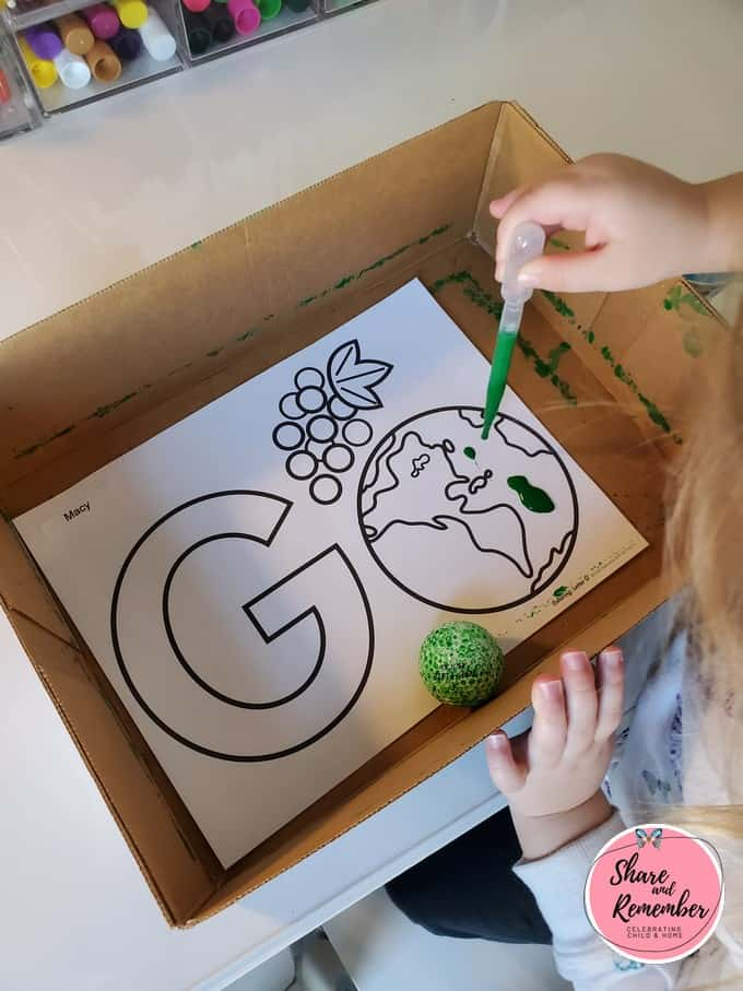 Rolling a golf ball through paint in a box on letter G alphabet page.