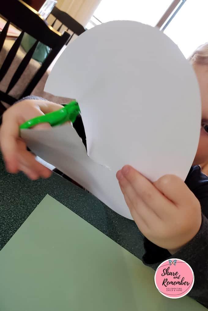 Cutting a crack in a paper egg.