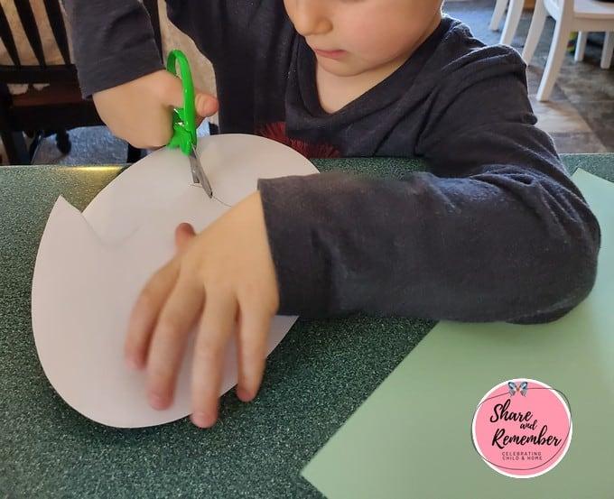 Preschooler cutting paper egg.