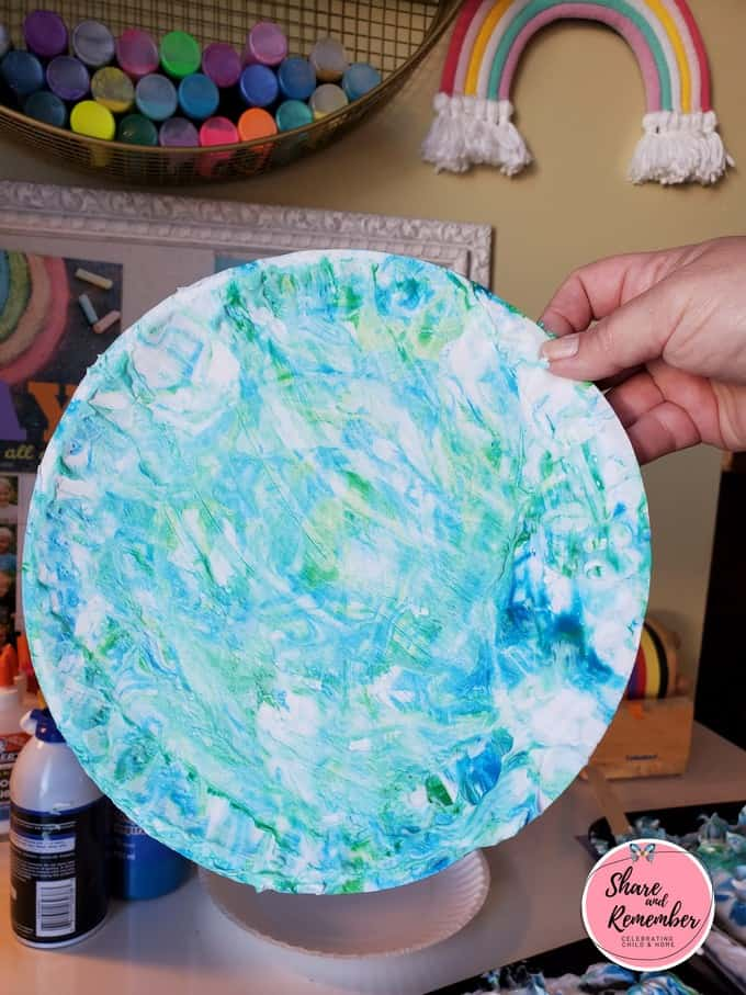 Paper plate globe art created with shaving cream and blue and green paint.