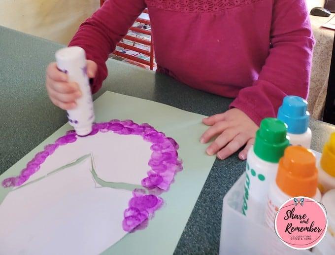 Preschooler painting an egg shape with a dot painter bottle.
