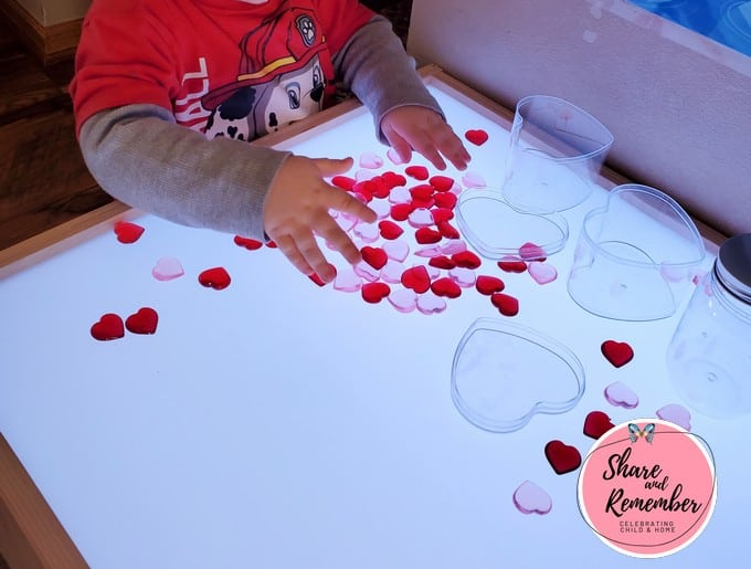 playing with hearts on the light table in preschool