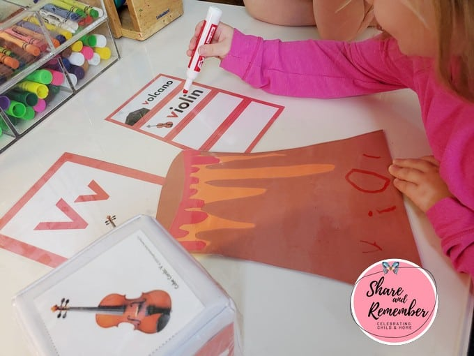 child writing the word violin.