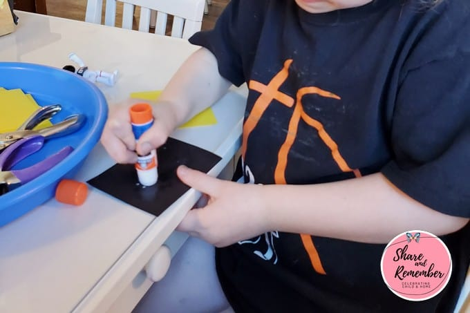 Child gluing paper together using glue stick.