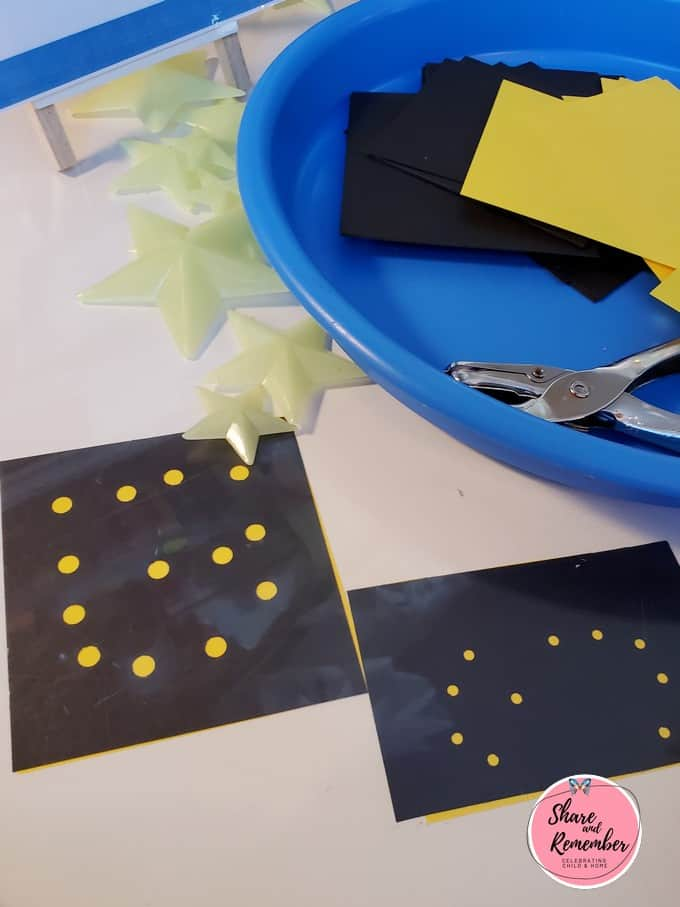 Hole punched constellation on black and yellow paper.