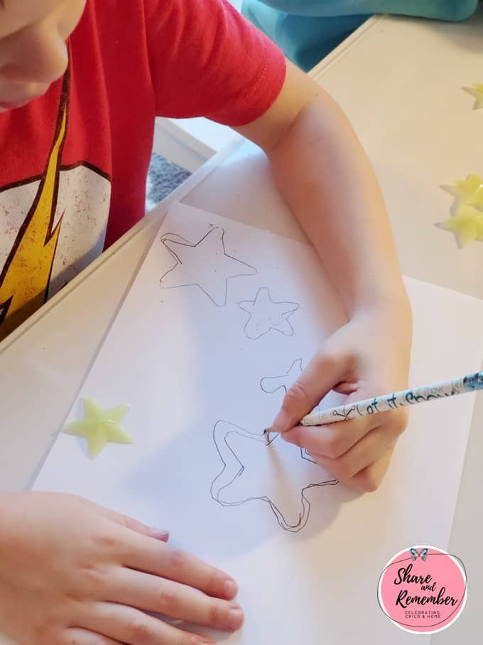 Child outlining star shape with a pencil.