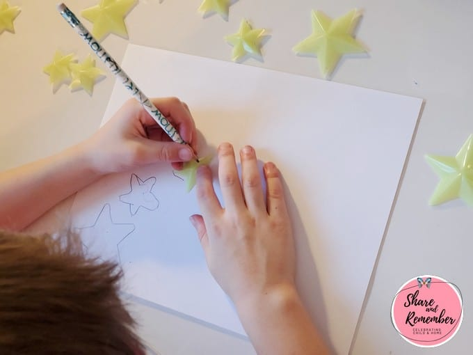 Child tracing a star shape with a pencil.