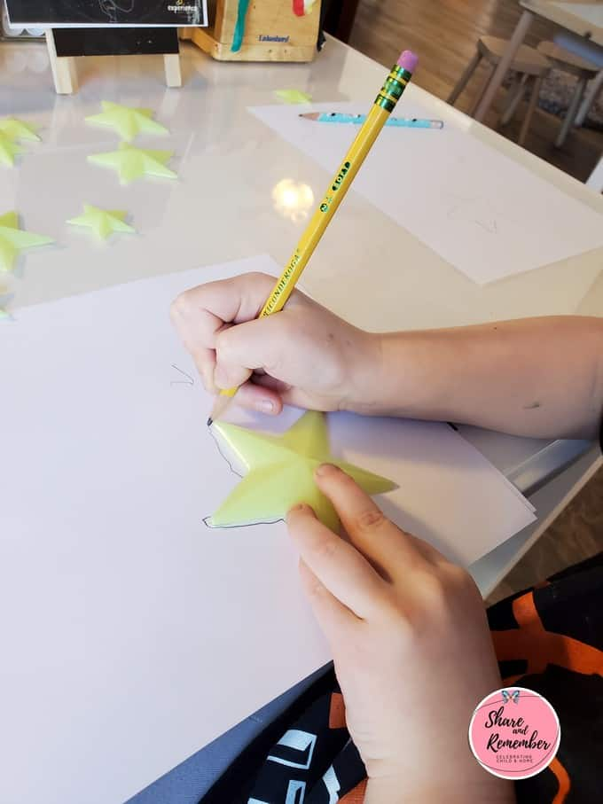 Child tracing a star shape.