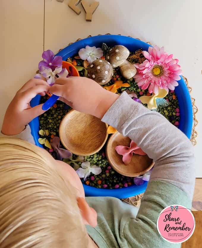 Child chooses items out of sensory tray using tweezers