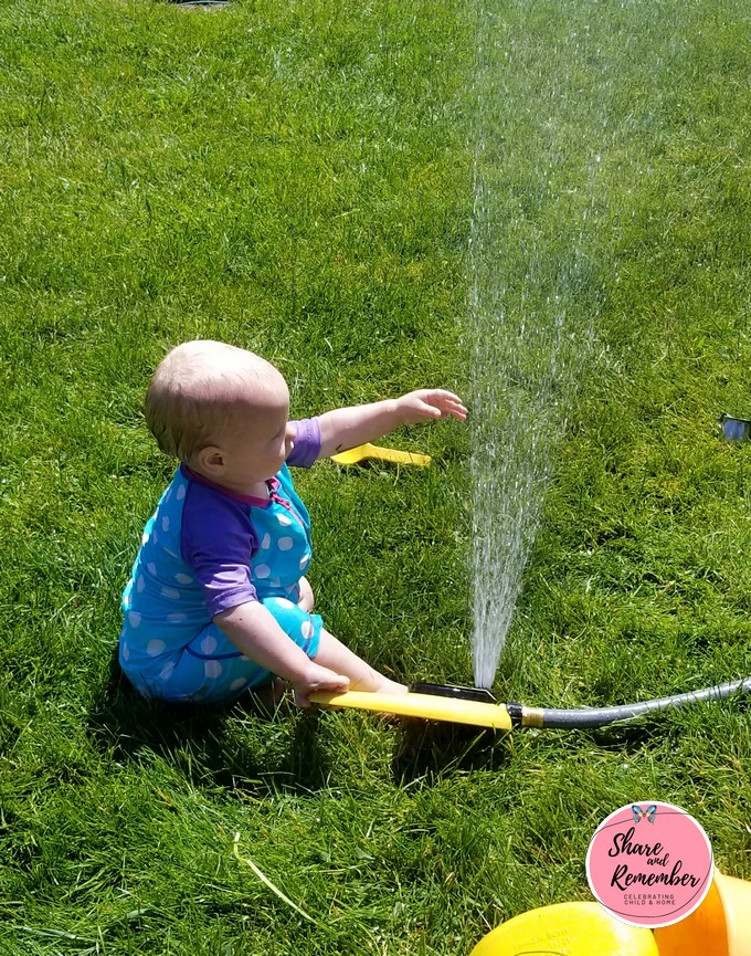 baby playing with sprinkler